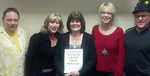 Grand Prize winner Mary Jo Cook of Munising flanked by the Holiday Travel and GLR staff.